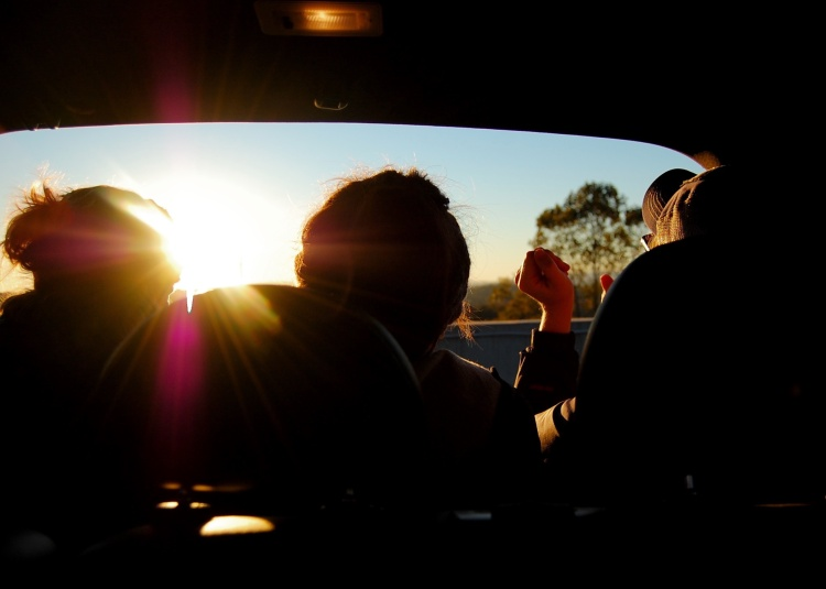 silhouette road trip with friends while sunsets across highway